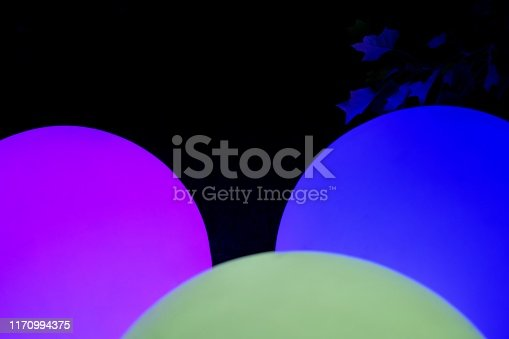Fragments of three purple, light green and blue balls glowing in three colors and a dark branch in the dark.