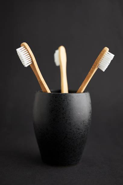 Tres cepillos de bambú en un cristal negro - foto de stock