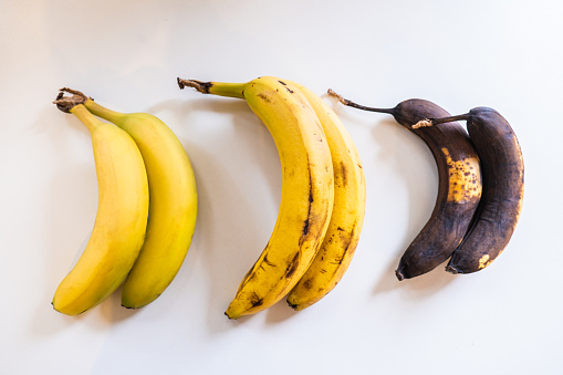 Three bananas of different maturity on white table