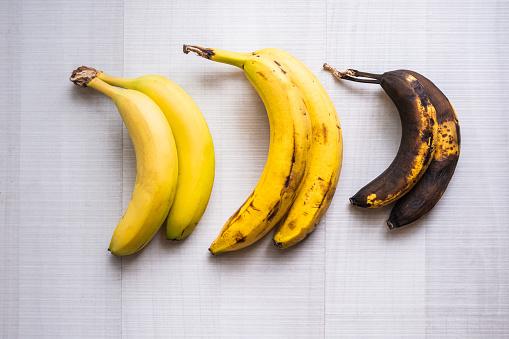 Three bananas of different maturity on white ground