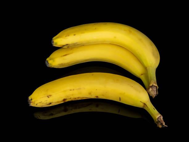 0570 drei Bananen auf einem schwarzen Hintergrund mit Spiegelung – Foto