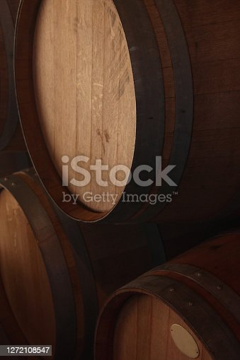 tres barriles de vino de madera de roble apiladas , con luz rasante tenue en deposito, almacén de bodegas de vino, en San Rafael, provincia de Mendoza, Argentina