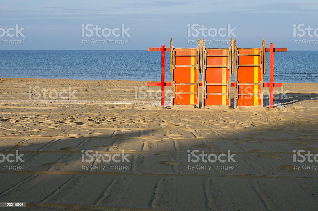 Three Beach Chairs against Blue Sea and Sky on Sand stock photo
