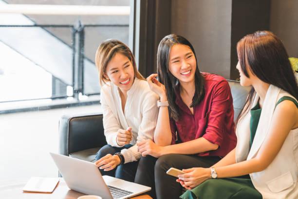 3 美しいアジア女の子は一緒にカフェやコーヒー ショップでソファでおしゃべり。ゴシップ話、ガジェットの技術、スタートアップ中小企業、大学の学生や働くビジネス女性概念でカジュアルなライフ スタイル - 大学生 パソコン 日本 ストックフォトと画像