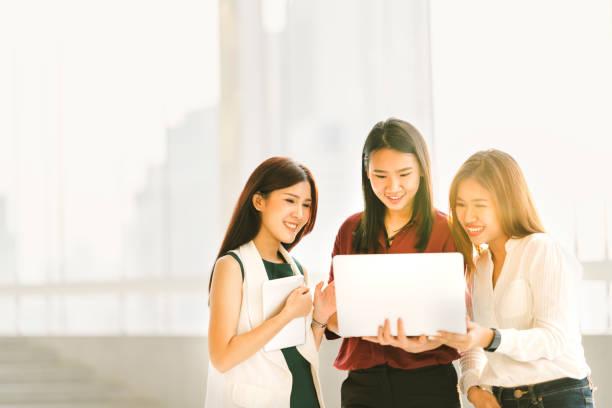 カジュアルなビジネス ラップトップ ノート ブックとデジタル タブレット ガジェットの技術や働く女性の概念、日没、モダンなライフ スタイルでの会議で 3 つの美しいアジアの少女をコピー スペース - 大学生 パソコン 日本 ストックフォトと画像