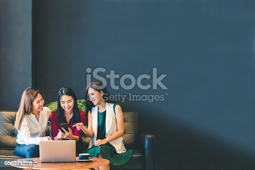 istock Three beautiful Asian girls using smartphone and laptop, chatting on sofa at cafe with copy space, modern lifestyle with gadget technology or working woman on casual business concept 686371228