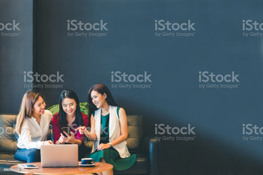 Three beautiful Asian girls using smartphone and laptop, chatting on sofa at cafe with copy space, modern lifestyle with gadget technology or working woman on casual business concept stock photo
