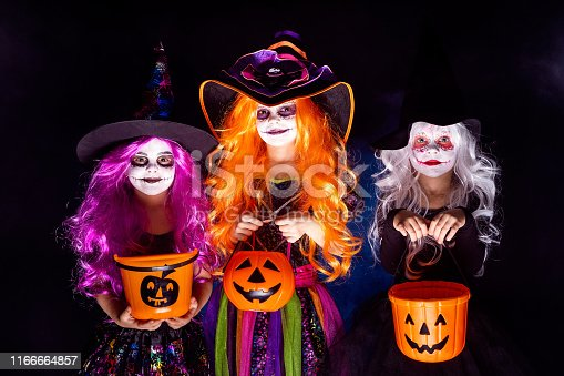 istock Three Beautiful girl in a witch costume on a dark background in smoke scaring and making faces 1166664857