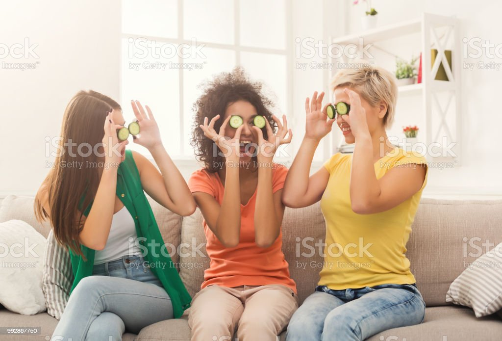 Three beautiful girls covering eyes with cucumber - foto stock