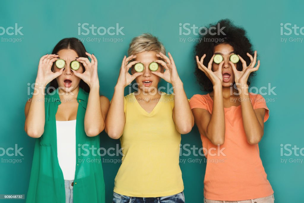 Three beautiful girls covering eyes with cucumber pieces stock photo