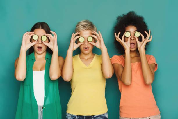 drei schöne mädchen für augen mit gurke stücke - gurke gesund stock-fotos und bilder