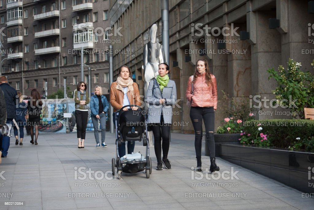 Three beautiful girls on White Square office center in Moscow, Russia. stock photo