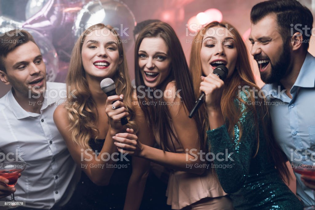 Three beautiful girls sing in a karaoke club. Behind them are men waiting for their turn. stock photo
