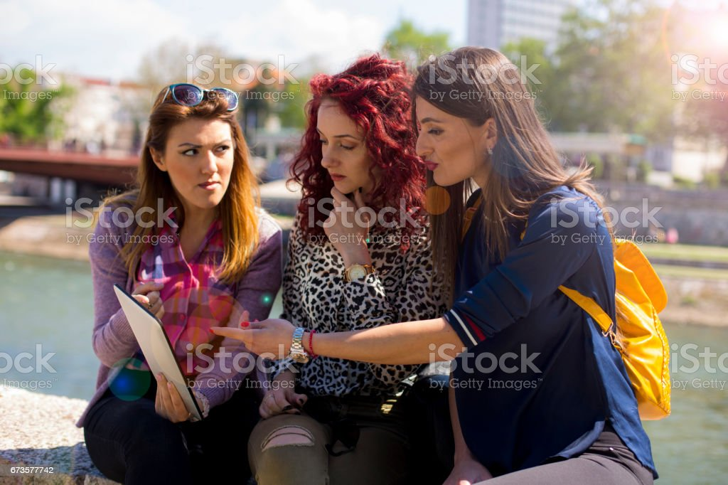 Three beautiful girls using digital tablet in a park stock photo