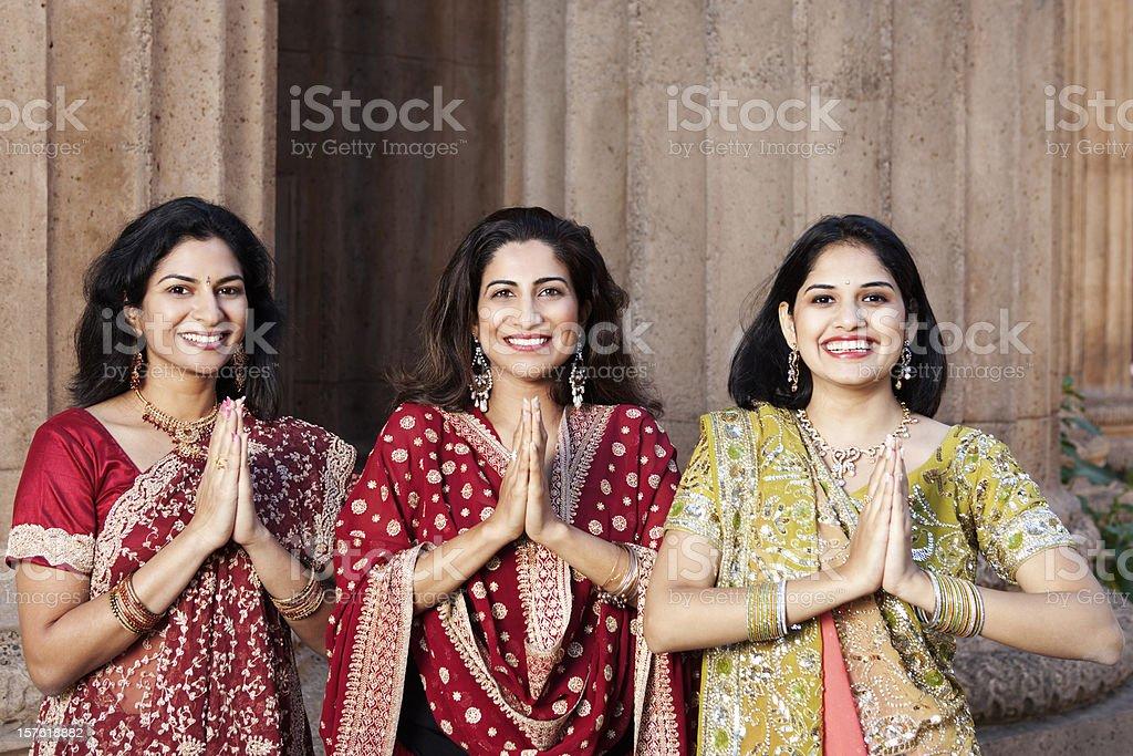 Three beautiful Indian women in traditional saris greeting namaste stock photo