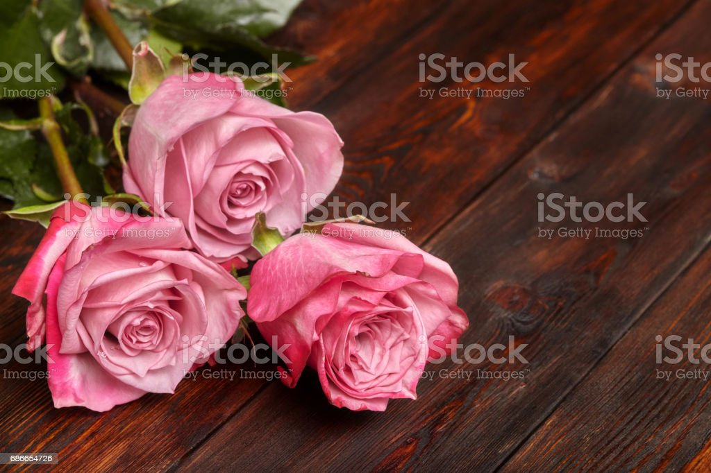 Three beautiful pink roses on wooden table, romantic background royalty-free stock photo
