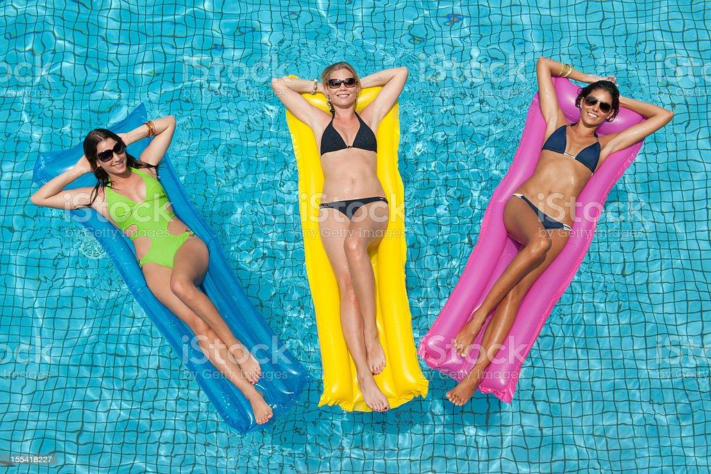 Three Beautiful Women sun bathing at the Pool (XXXL) stock photo