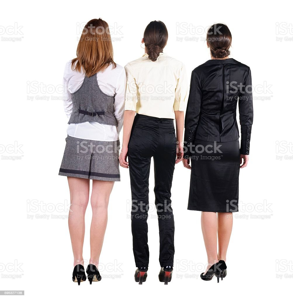 three beautiful young bussineswoman looking at wall. Rear view. stock photo