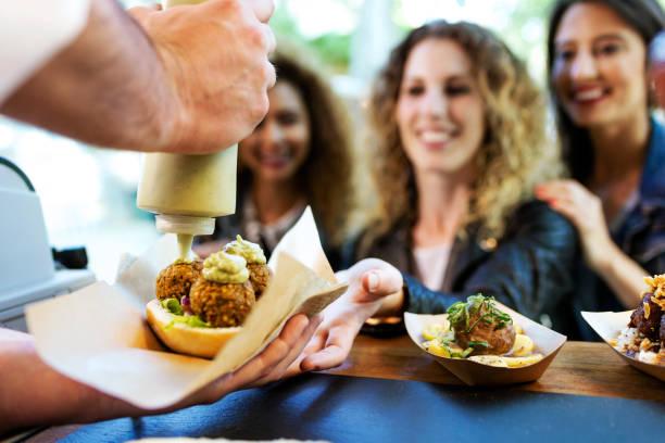 Drei schöne junge Frauen, die Fleischbällchen auf einem Food-Truck kaufen. – Foto