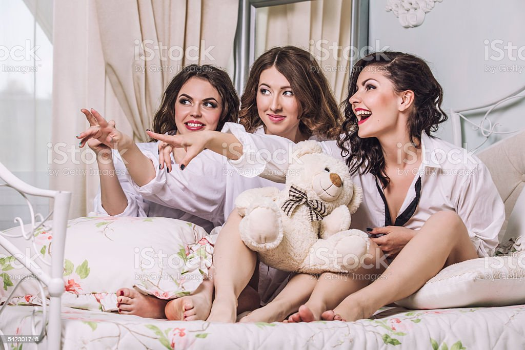 Three beautiful young women friends chatting in the bedroom stock photo