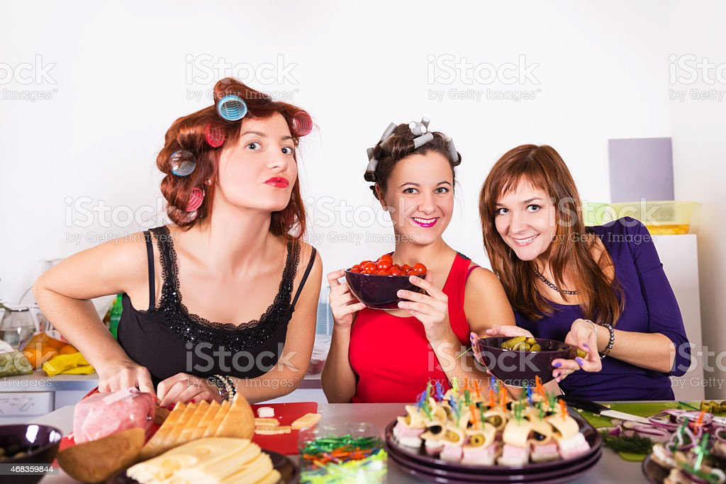 Three beautiful young women housewifes cook together royalty-free stock photo