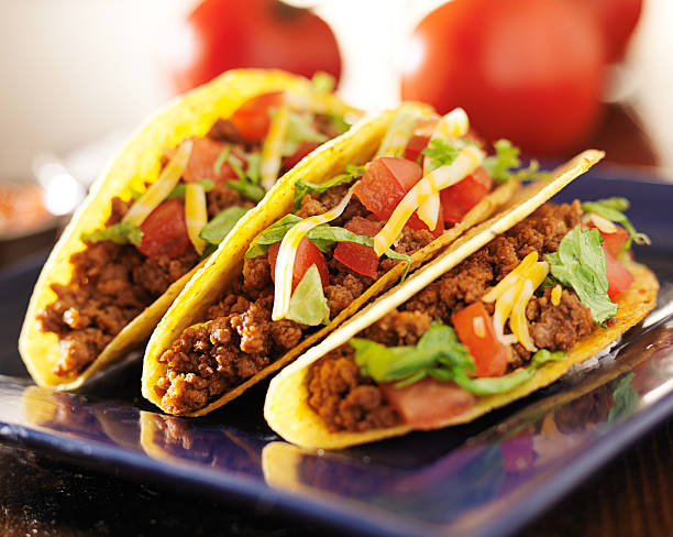 three beef hars shell tacos with cheese, lettuce and tomatoes stock photo