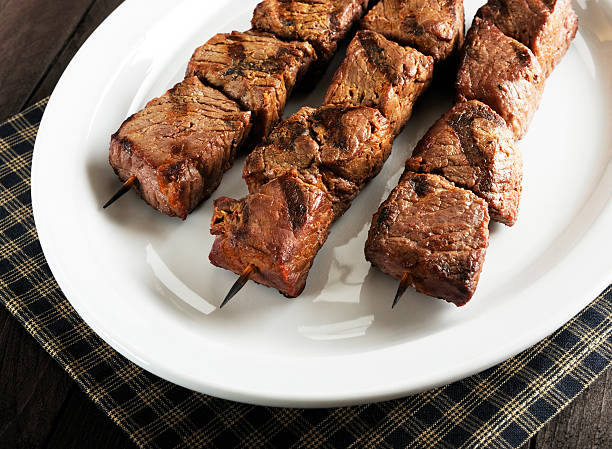 Three beef kebabs arranged on a white platter stock photo