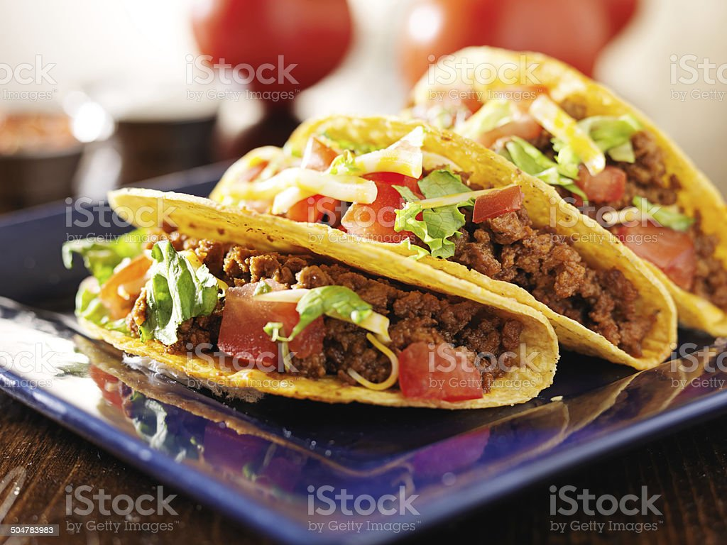 three beef tacos with cheese, lettuce and tomatoes stock photo