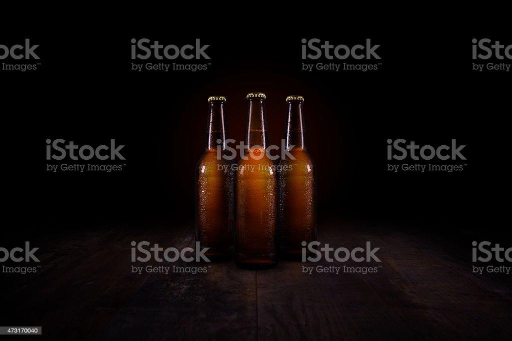 Tres botellas de cerveza en un ambiente rústico mesa de madera - foto de stock