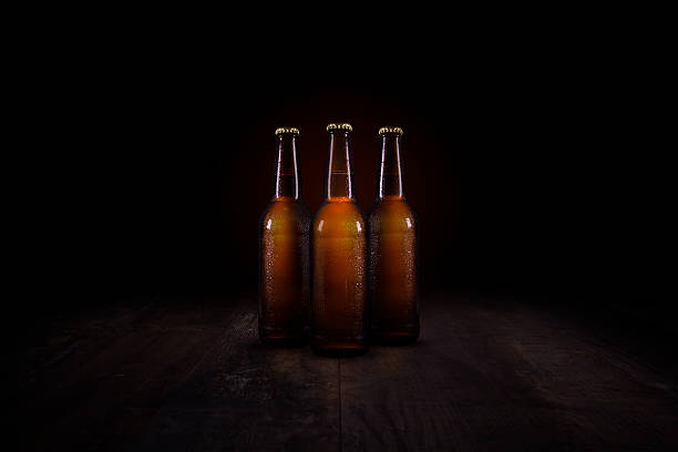 Three beer bottles on a rustic wooden table stock photo