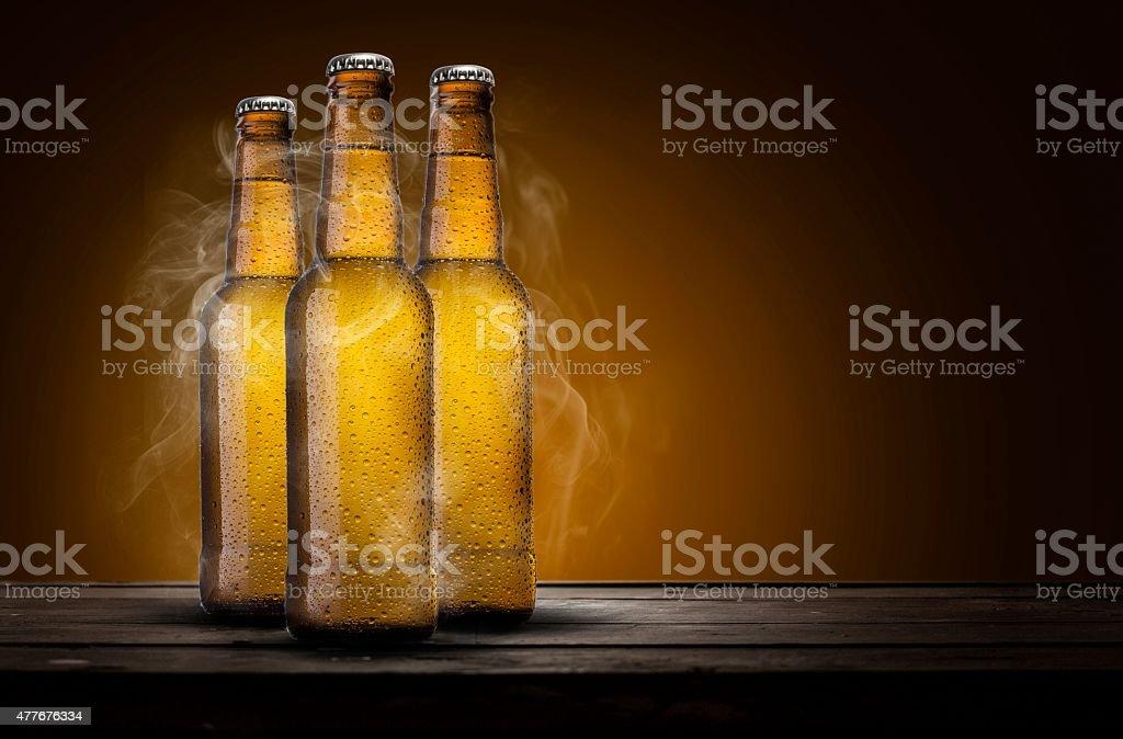 Drei Biersorten mit coolen Rauch über Holztisch – Foto