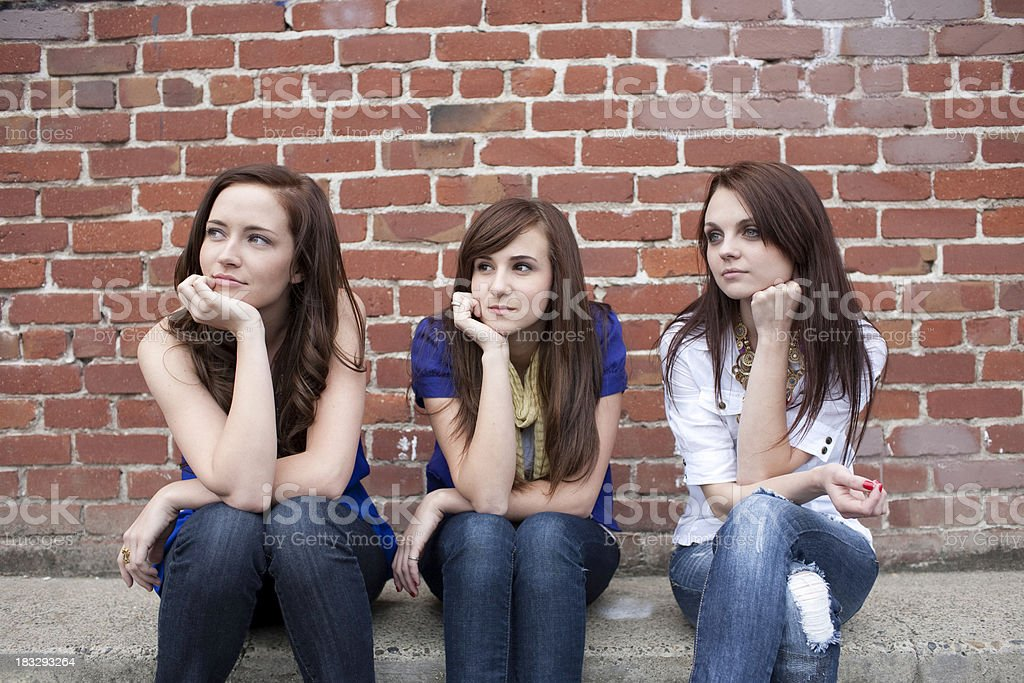 Three best girl friends sitting outdoors looking away royalty-free stock photo