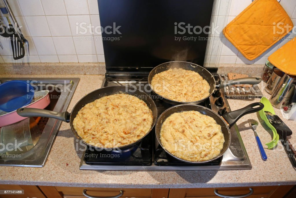 three big pans with the food named frico a typical italian dish stock photo