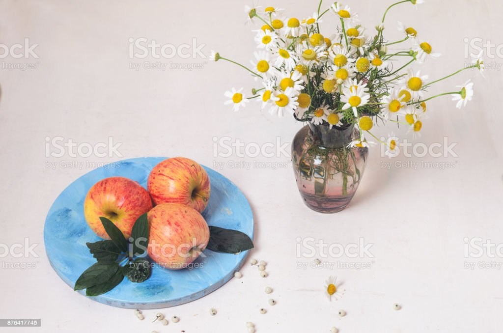 Three big red apples lie on a round wooden board stock photo