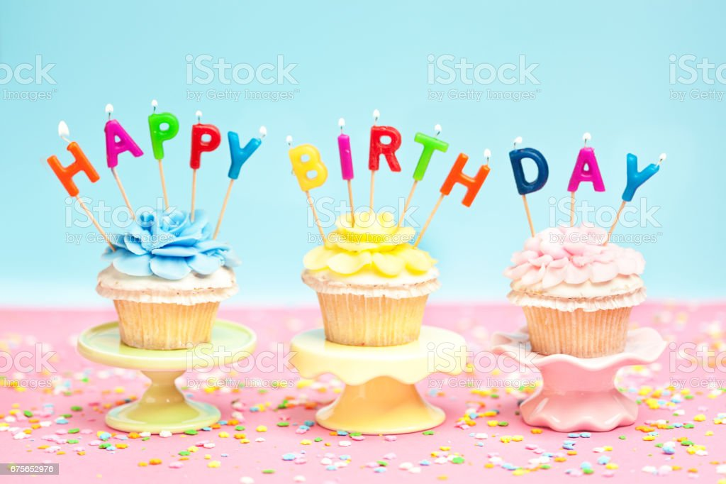 Three Birthday Cupcakes with Candles and Confetti on Pink Background stock photo