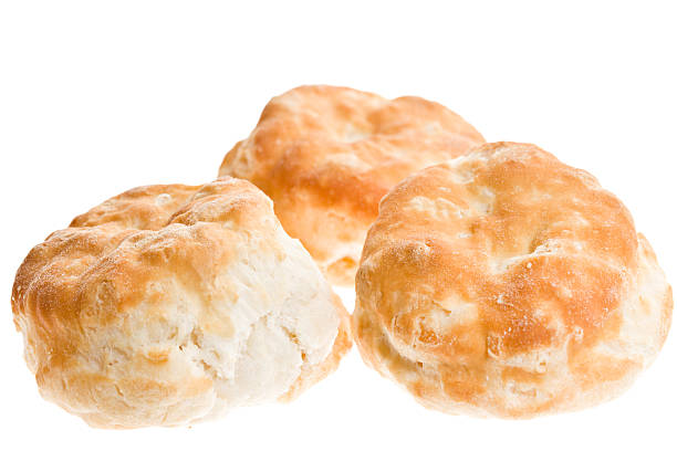 Three Biscuits A high angle close up of three freshly baked golden brown buttermilk biscuits. Isolated on white. biscuit stock pictures, royalty-free photos & images