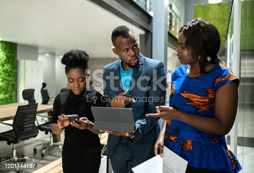 Three black african colleagues walking through coworking workspace strategizing on their way to boardroom business meeting