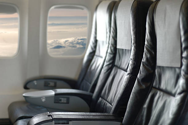 Three black aircraft seats looking out of the window stock photo