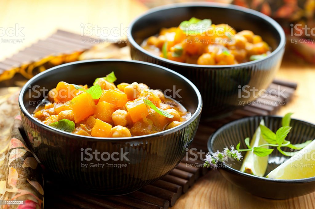 Three black bowls filled with pumpkin curry and side dishes stock photo