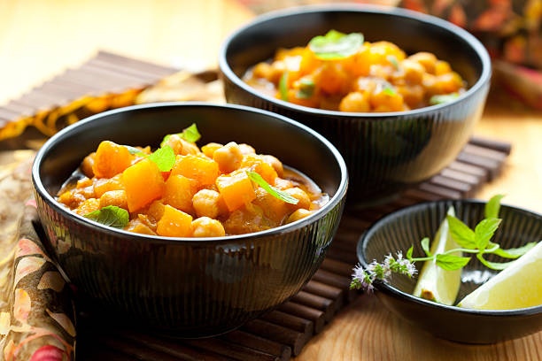 Three black bowls filled with pumpkin curry and side dishes Pumpkin curry with chick-peas curry powder stock pictures, royalty-free photos & images