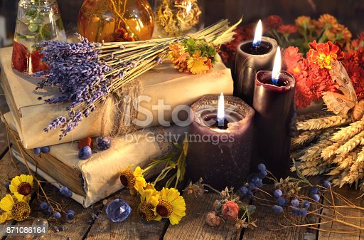 811119304 istock photo Three black candles, lavender bunch, healing herbs and flowers 871086164
