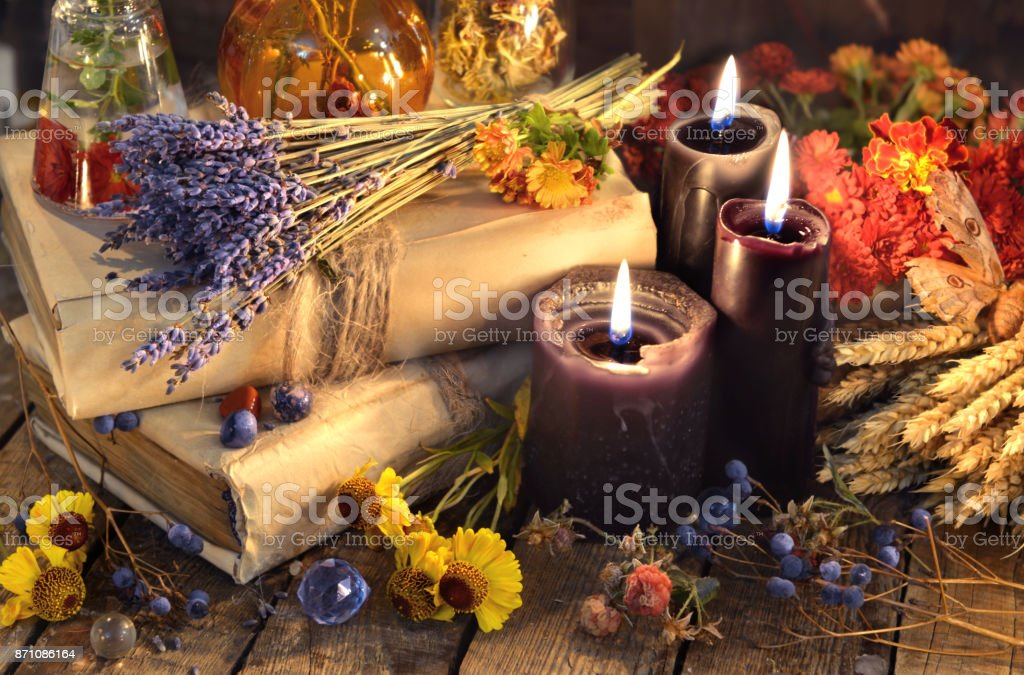 Three black candles, lavender bunch, healing herbs and flowers stock photo