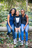 A group of three black girls smiling for the camera outdoors