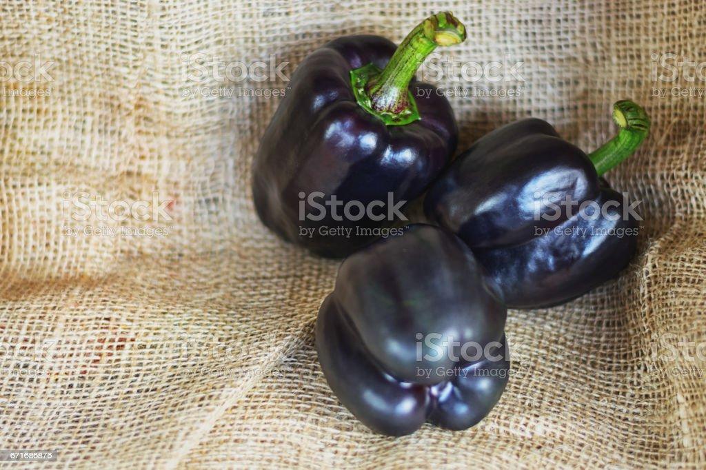 three black paprika's on a piece of jute stock photo