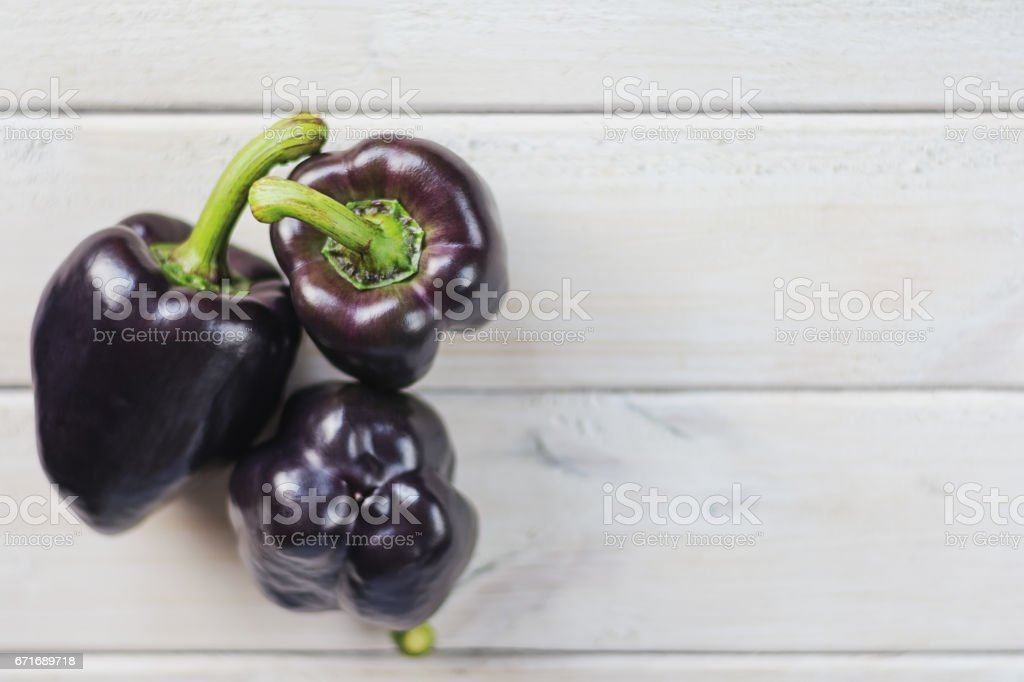 Three black paprika's on a white wooden board stock photo