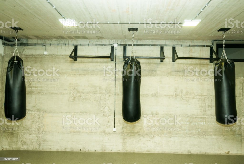 Three black punching bags in the empty boxing gym with naked grunge wall in background stock photo