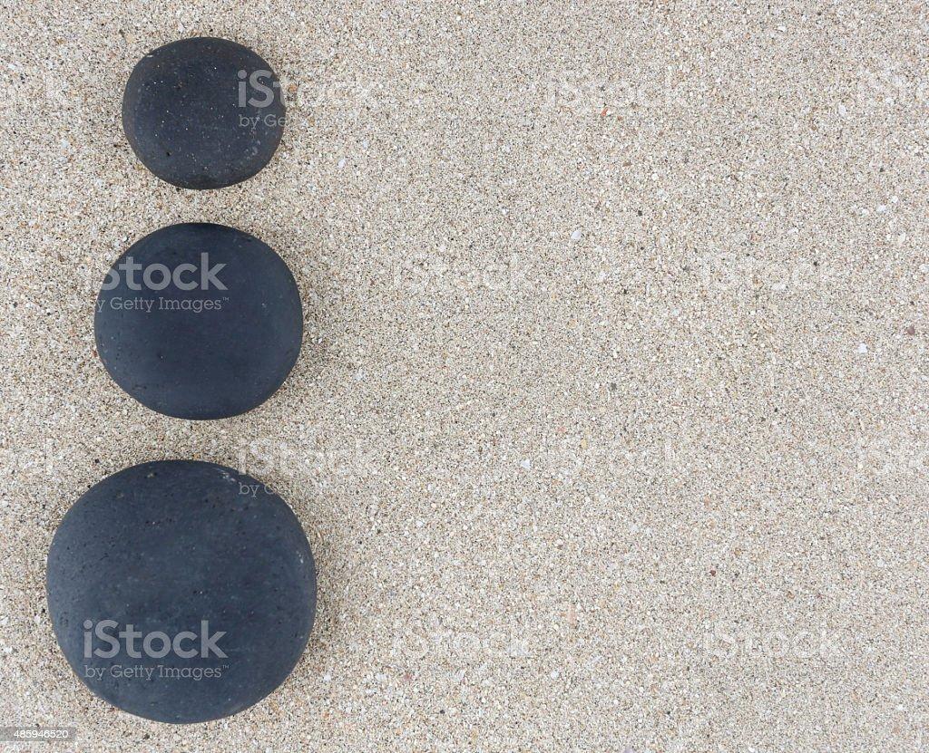 Three black zen stones at left side of sand background stock photo
