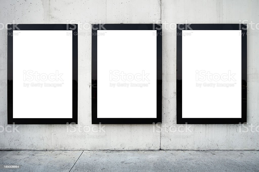 Three blank billboards on wall. stock photo