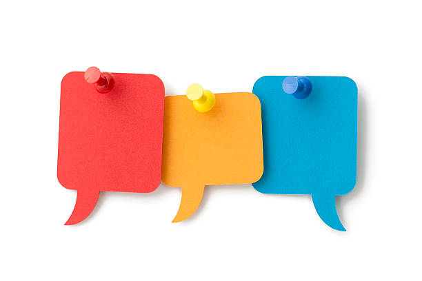 Three blank colourful speech bubbles pinned to a white surface stock photo