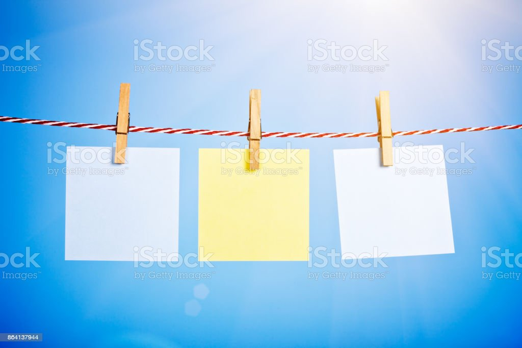 Three blank message slips pinned to sunny clothesline royalty-free stock photo